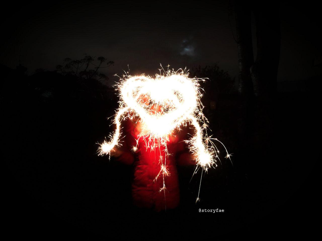 lightpainting in the dark with sparklers making a heart